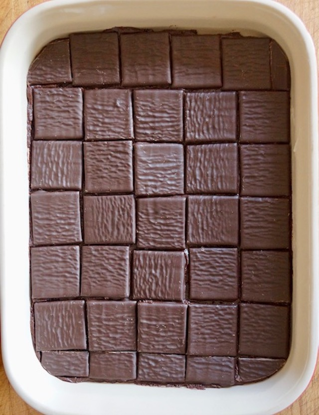 After Eight mint thins completely coating a layer of brownie batter in a baking pan