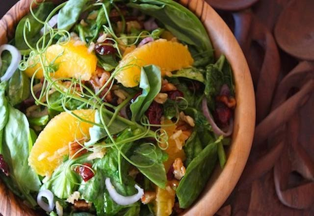 Snow Pea Shoot Salad with Spicy Pecan Dressing in a wooden bowl