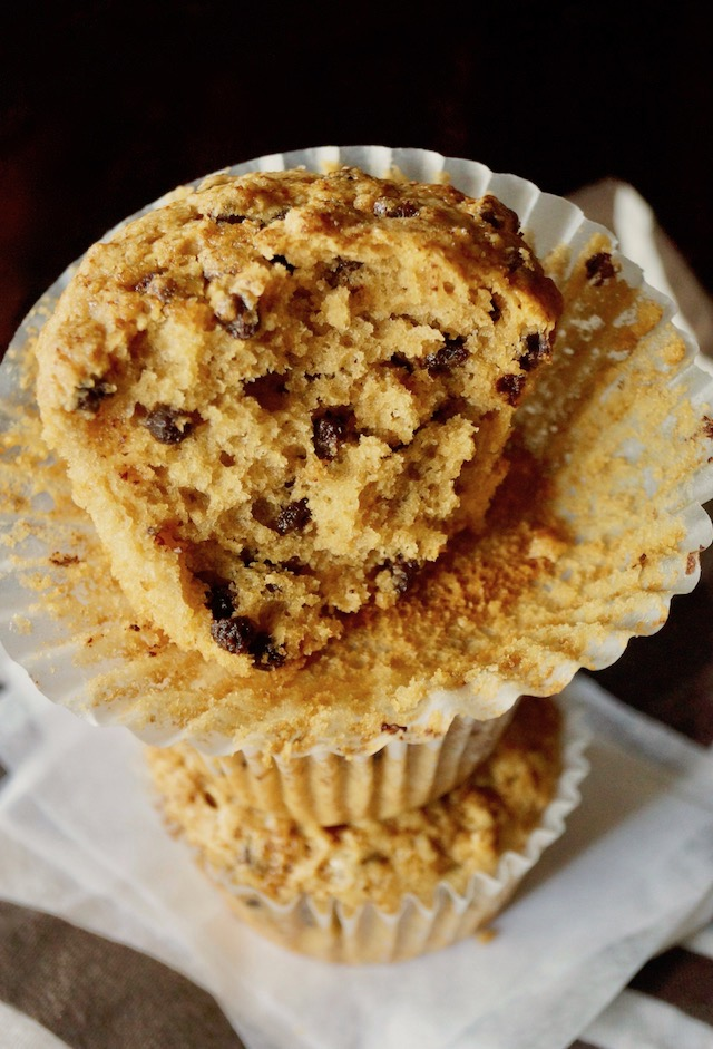 Cappuccino Muffins with chocolate chips in a stack with the top one half gone