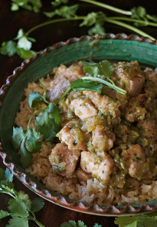 Puerco Con Salsa Verde in a green bowl with fresh cilantro sprigs