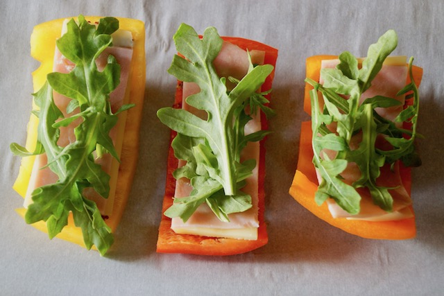 3 slices of bell peppers, yellow, red and orange with ham and arugula for Breadless Bell Pepper Grilled Ham and Cheese Sandwich Recipe.