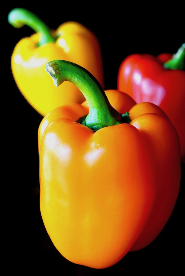 3 bright bell peppers on black background, red, orange and yellow.