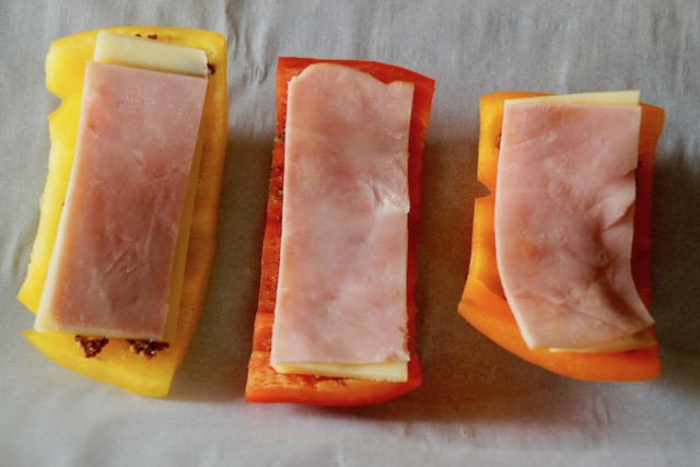 Sliced of red, yellow and orange bell peppers with ham slices on parchment for Breadless Bell Pepper Grilled Ham and Cheese Sandwich Recipe.