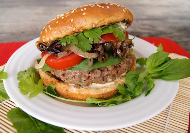 One Spicy Grilled Sriracha Burger on a white plate with fresh herbs.
