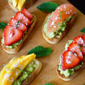 4 slices of avocado toast with mango, grapefruit and strawberries