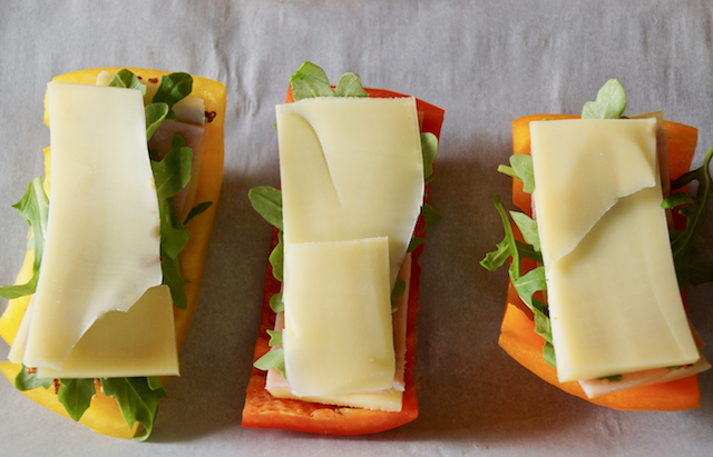 Slices of bell peppers with arugula and slices of cheese, on parchment.