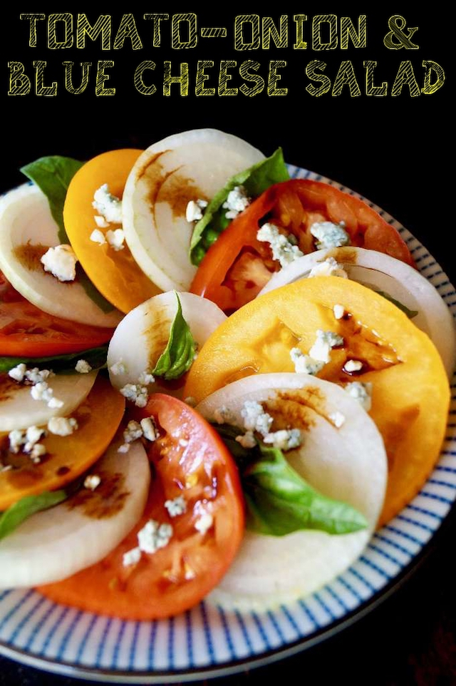 red and yellow Summer Tomato-Sweet Onion Salad with Blue Cheese and fresh basil on pretty blue plate