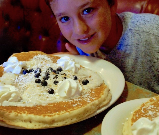 cute boy with giant pacake with whipped cream and chocolate chips