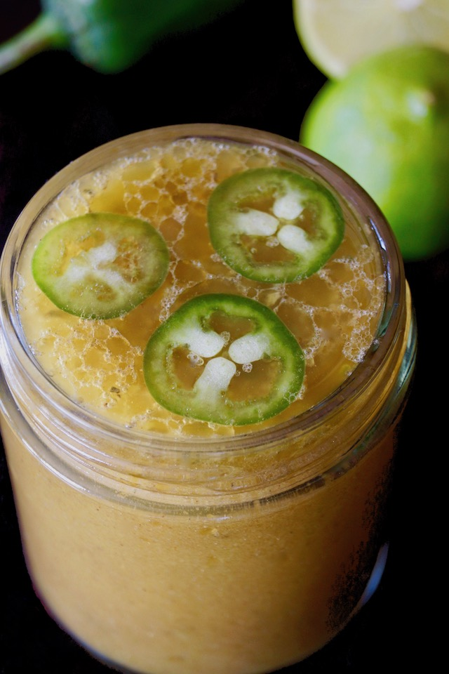 Creamy Roasted Jalapeno-Lime Vinaigrette in a jar with three round jalapeno slices
