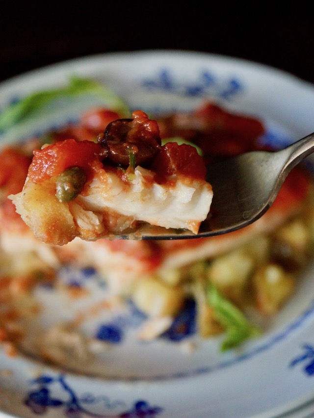 One bite of white fish on a fork with a little tomato and olive slice