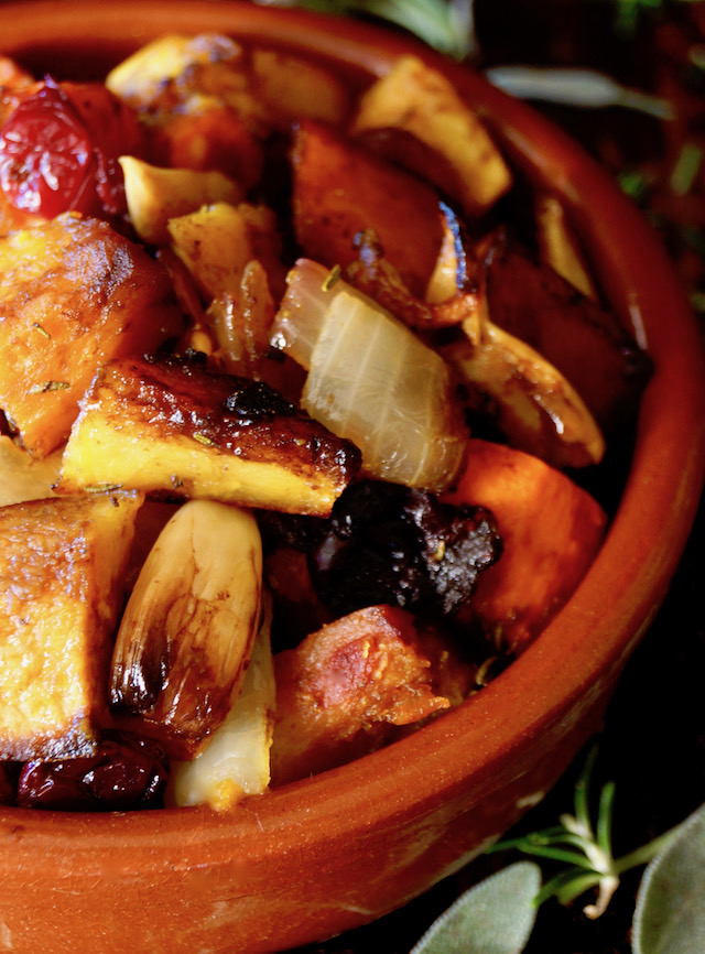 Roasted Balsamic Cranberry Fall and Winter Squash in a round terracotta dish surrounded by sage leaves