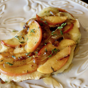Caramelized Apple Brie Melt on white plate with thyme