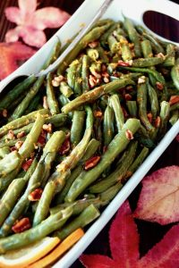 green beans with pecan pieces in white serving dish with red maple leaves in background