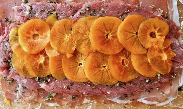 thinly sliced presimmon on butterflied pork tenderloin, on plastic wrap
