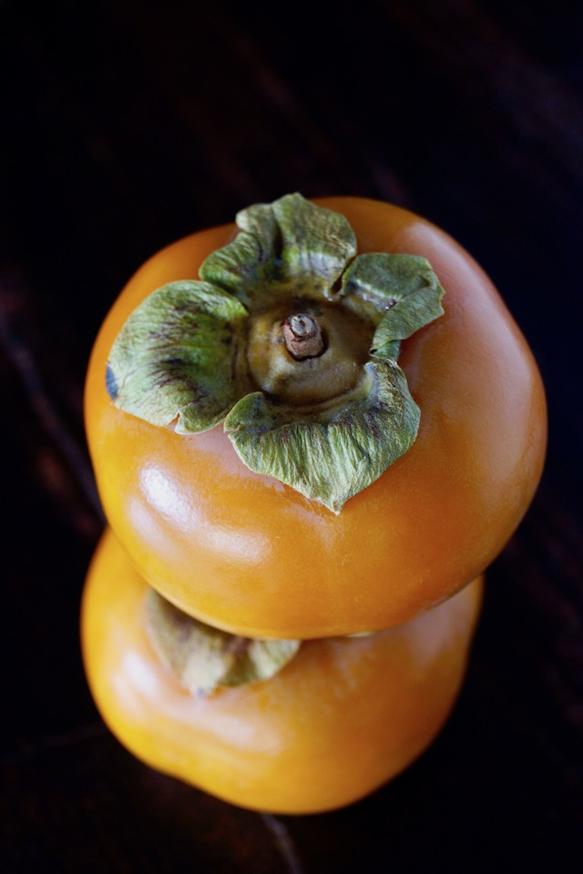 two Fuyu persimmons, one on top of the other for Persimmon Prosciutto Pork Tenderloin Recipe
