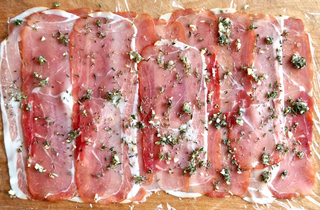 Thin slices of prosciutto with rosemary on top