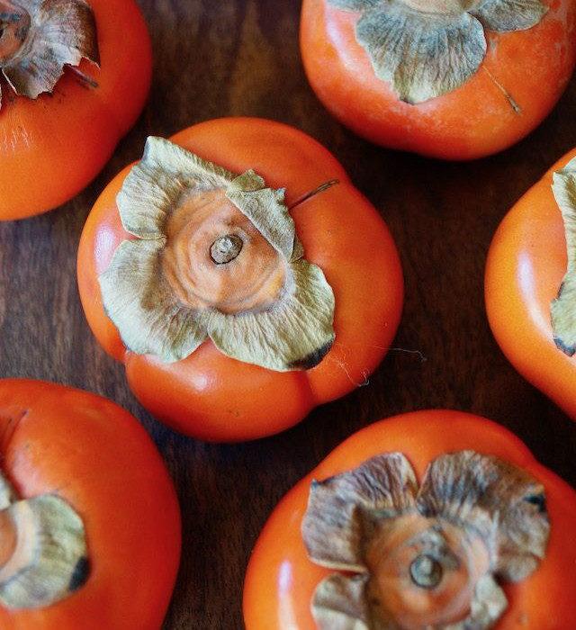 several dark orange persimmons on wood surface