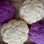 2 purple raw and 2 white raw cauliflower, round side up in a baking dish