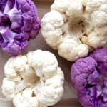 2 purple raw and 2 white raw cauliflower, rooot side up in a baking dish