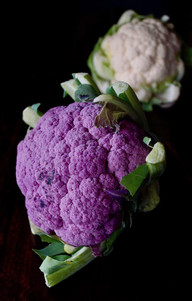 raw purple cauliflower with small white, raw cauliflower in background