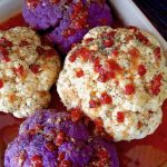 2 purple and 2 whtie raw cauliflower surround by light red sacue and topped with bits of red pepper, in a baking dish