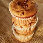Stack of 3 gluten-free peanut butter banana muffins with mini chocolate chips, on a burlap background.