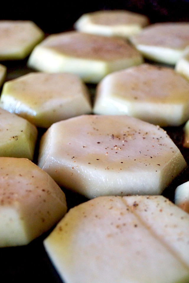 Several slices of raw kohlrabi on a baking sheet with salt, pepper and olive oil, for Simple Perfect Roasted Kohlrabi