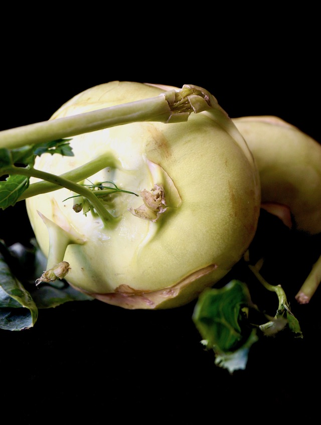 Raw, whole Kohlrabi on its side with stems and leaves for Simple Perfect Roasted Kohlrabi.