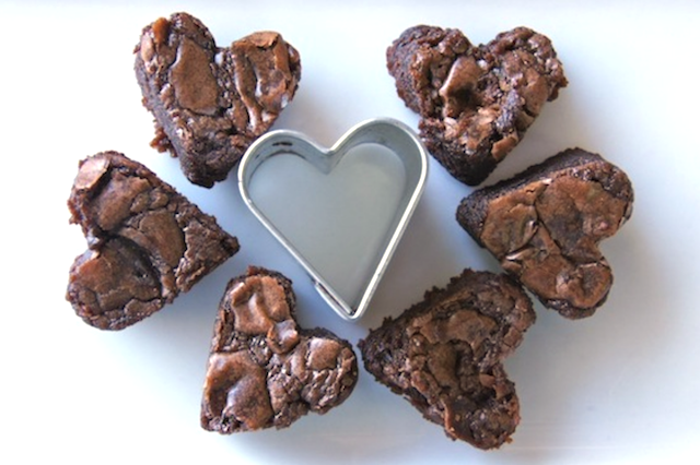Six tiny Nutella Brownies in heart shapes, surrounding a small metal heart cutter.