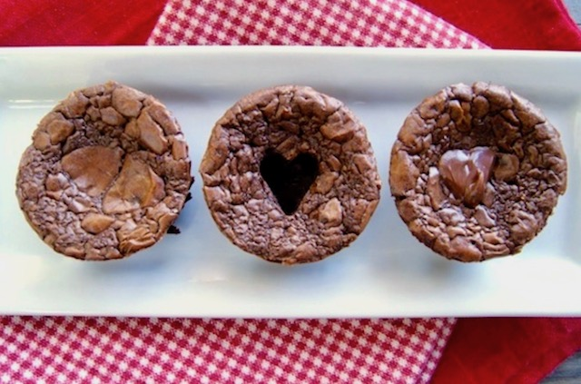 Three round Nutella Brownies on a narrow whate plate. One whole, one with a heart cut-out and one with heart full of Nutella.