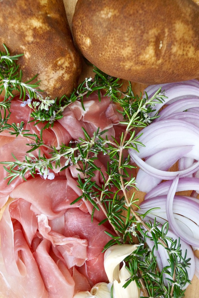 Display of ingredients -- prosciutto, slices of raw onion, fresh rosemary sprigs and two Idaho potatoes.