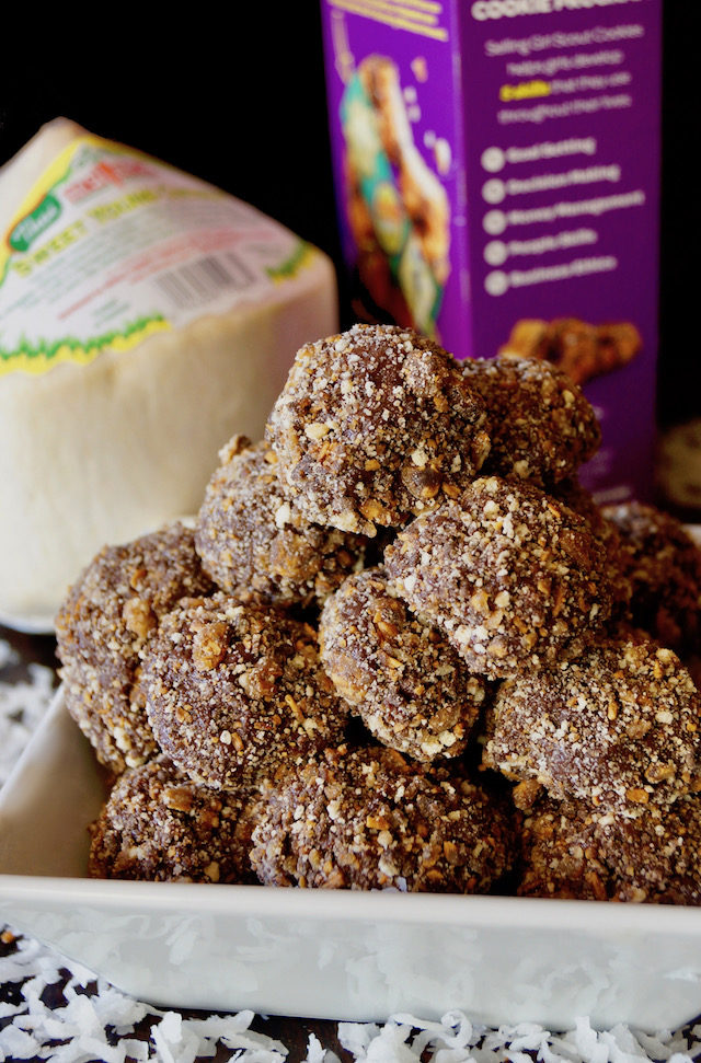 Samoa Chocolate Coconut Truffles piled up in a white dish with a box of samoas and a coconut in the background.
