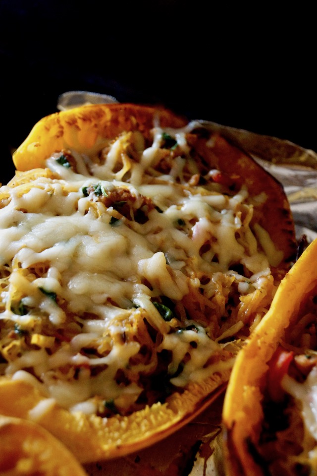 One half of a Spinach-Sausage Stuffed Spaghetti Squashon a baking sheet with foil..