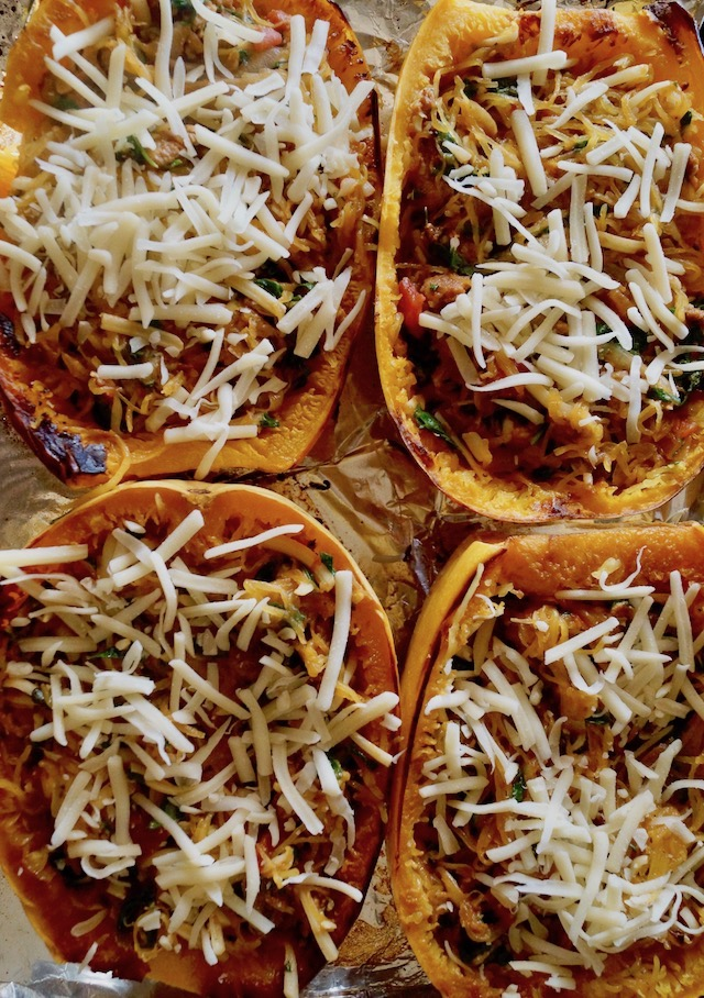 Four halves of Spaghetti squash filled with spinach, sausage and topped with cheese.
