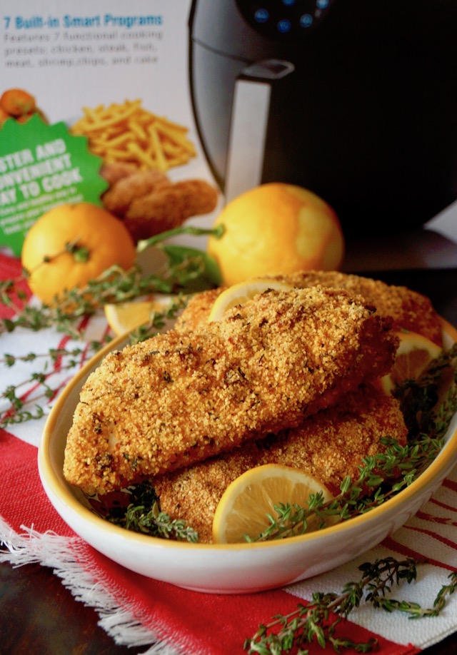 Yellow rimmed bowl full with Air Fryer Gluten-Free Lemon Fried Chicken breasts, and GoWISE air fryer box.