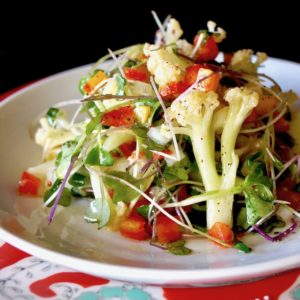 Fioretto Recipes - Lemon Marinated Fioretto Salad on a white plate with a red plate beneath it.
