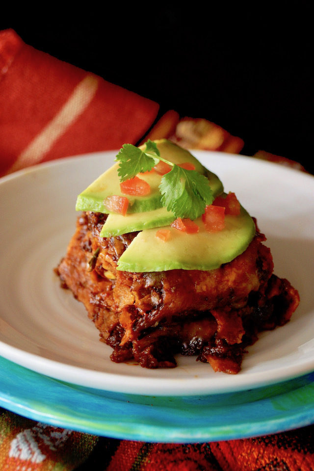 One vegetarian enchilada on a white plate with avocado slices and diced tomato.