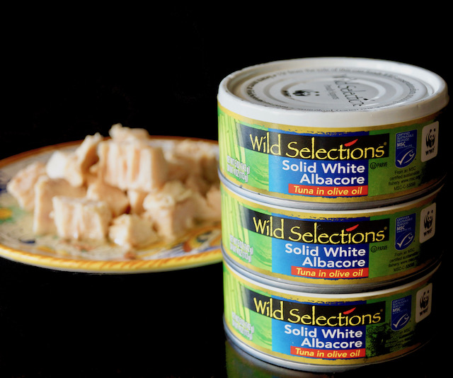 White Albacore tuna for Nicoise Deviled Eggs recipe on a plate with 3 cans of Wild Selections Tuna in front.