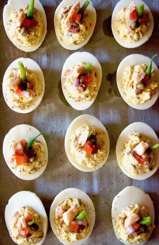 Nicoise Deviled Eggs lined up in rows on parchment paper.