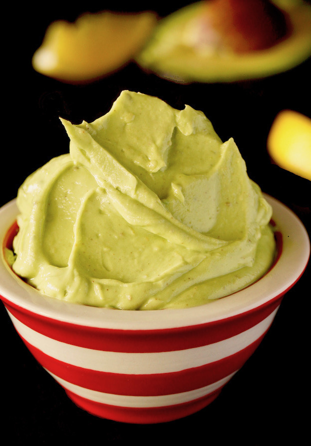 Avocado Butter rising above the top of a red and white striped bowl.