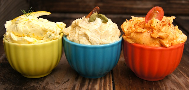 Three different compound butters in small yellow, blue and red bowls. (Meyer Lemon-Dill Butter, Spiced Chai Butter & Smoky Tomato Butter)