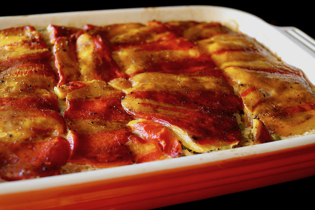 Top view of Enjoya Pepper Spring Lasagna, with an even coating on top of the peppers, roasted, in an orange baking dish.