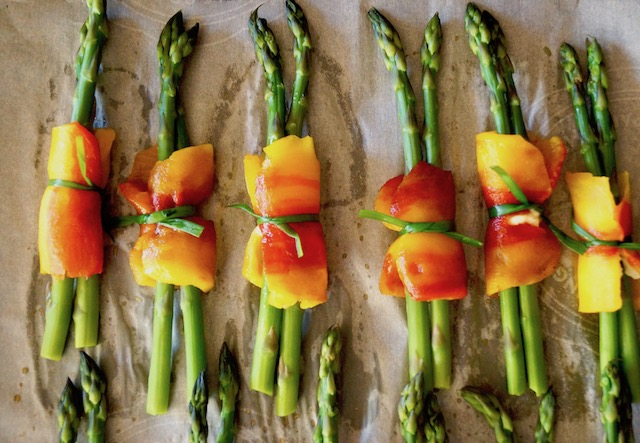 Several bundles of asparagus wrapped in the center with a roasted piece of an Enjoya pepper, and tied with a chive.