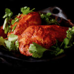 Achiote Chicken in black dish with cilantro