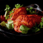 Marinated Achiote Chicken Recipe in black ceramic bowl with fresh cilantro.