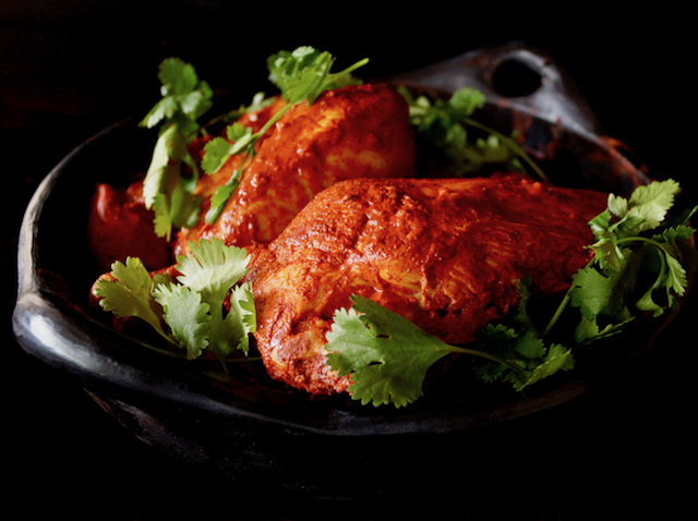 Marinated Achiote Chicken Recipe in black ceramic bowl with fresh cilantro.