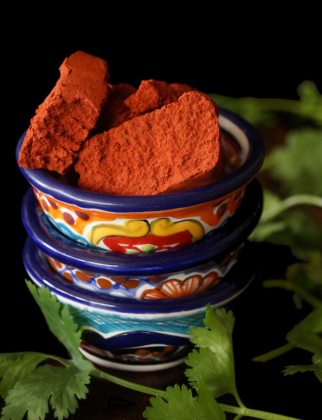 Small blocks of achiote paste fin pretty painted ceramic bowl, for Marinated Achiote Chicken Recipe.