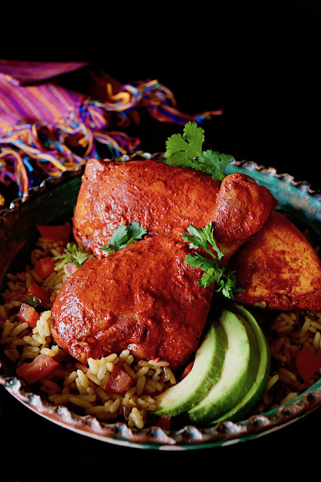 Drumstick and breast of Marinated Achiote Chicken Recipe with avocado slices and cilantro.