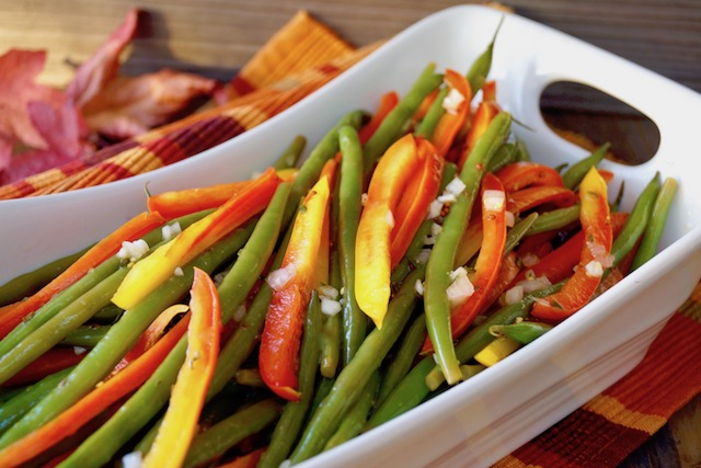White rectangular serving dish wtih strips of red-yellow Enjoya pepper and green beans.