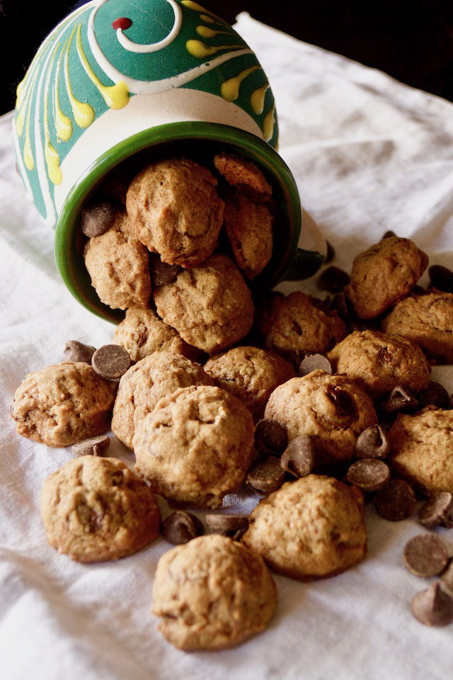 Mexican Chocolate Spice Cookies spilling out of a pretty, ceramic yellow and green mug onto a cloth napkin.
